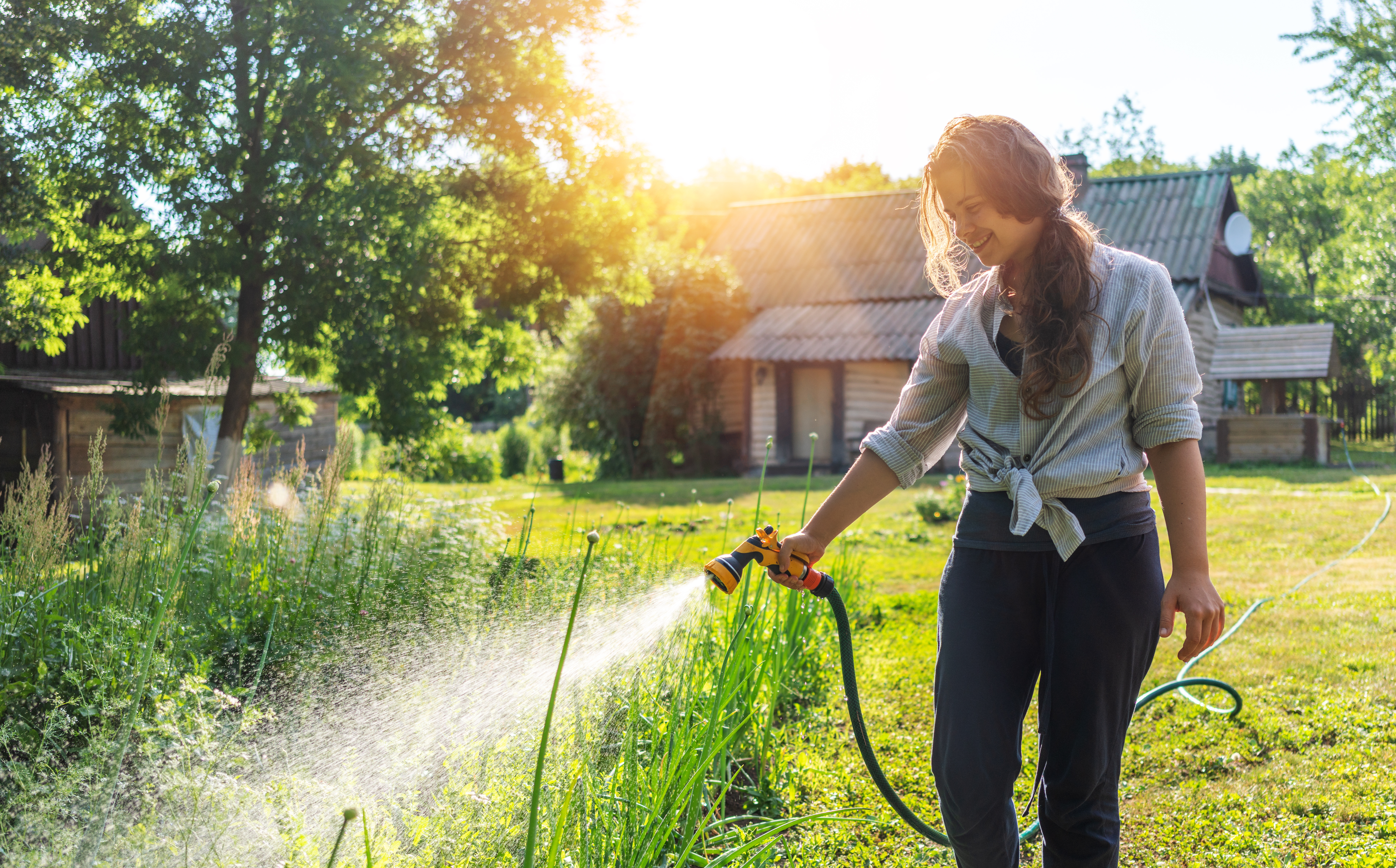 Woman watering her garden early morning